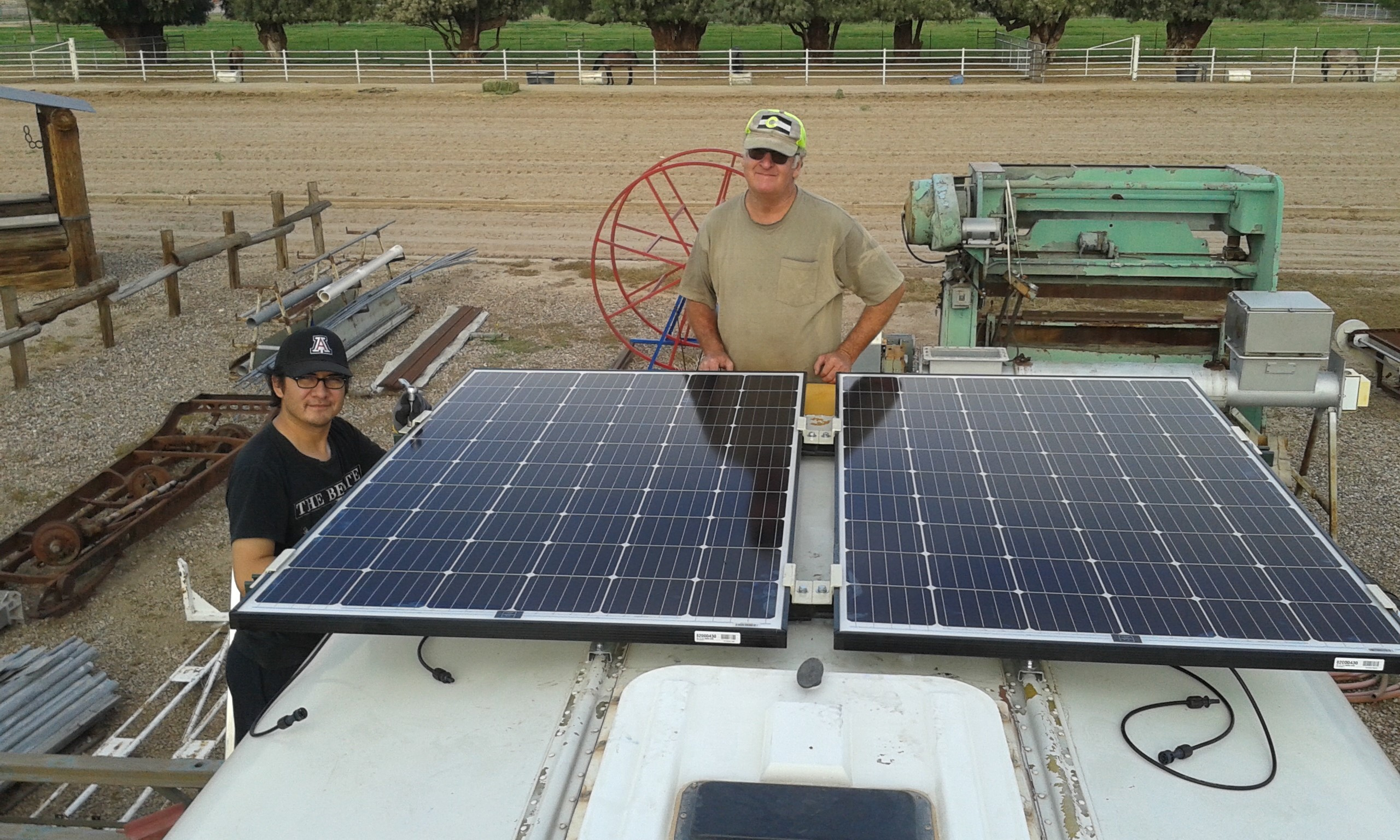 UA research associate Bob Seaman and Chris Yazzie, a master's degree student in environmental engineering, fasten solar panels to the roof of the bus that will purify water in Navajo Nation. (Photo: Rodolfo Peon)
