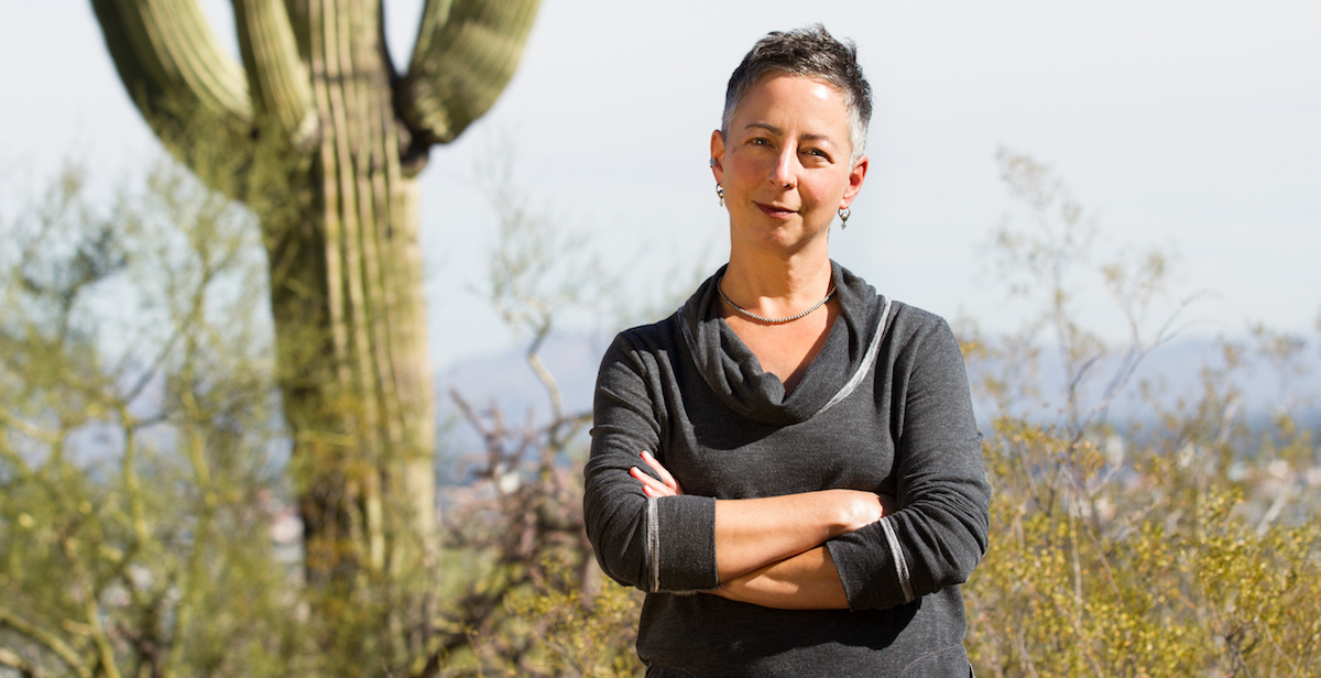 Tumamoc Arts Fellow Lyn Hart poses next to a Saguaro cactus.
