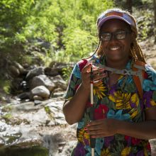 Earyn McGee holding a lizard in a dry stream bed in the Chiricahua Mountains