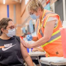 a young woman receives a vaccine