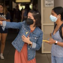 a woman wearing a mask points while another one woman in a mask looks in that direction