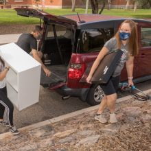 masked people moving furniture into a dorm