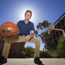 UA physicist Sam Gralla dribbles a ball on the basketball court.