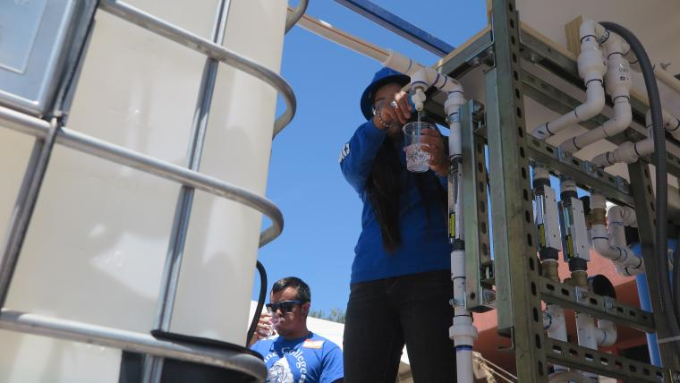 A Diné College student demonstrates use of the water filtration system.