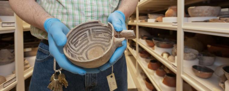 An art conservator is holding a native pot in the Arizona State Museum