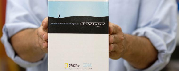 Matt Kaplan is holding a National Geographic box of the human journey the Genographic project