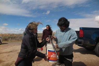 Graduate students in the Indige-FEWSS program fill buckets with well water and load them onto a pickup truck for use by a Diné family.