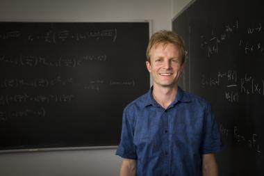 UA physicist Sam Gralla stands in front of two blackboards in his office.