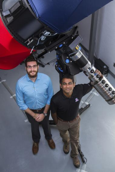 Vishnu Reddy (right) and Tanner Campbell (left) stand next to the RAPTORS telescope located at UA's Kuiper Space Sciences building. They would like to mount an optical sensor system on the telescope in the future.