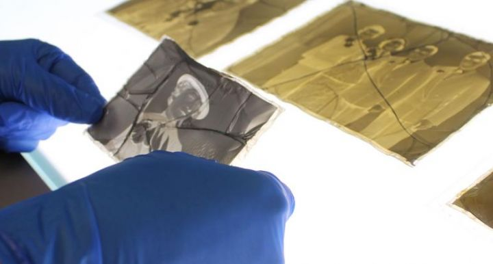 an old corroded photo negative is being examined by an art conservator with gloves on over a light box