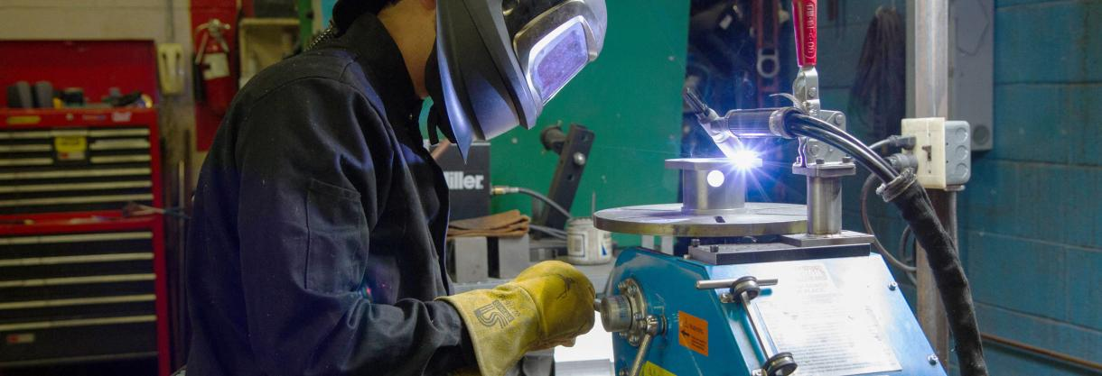 A welder is welding a hanger for the Giant Magellan Telescope at the University of Arizona's Machining and Welding shop
