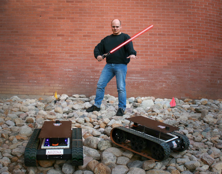 Wolfgang Fink holds a lightsaber and stands in between two of the Mars rovers built in his laboratory.